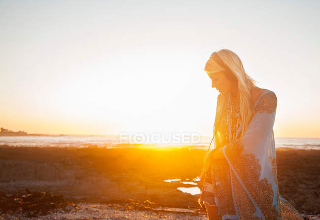 Woman on beach at sunset — Stock Photo