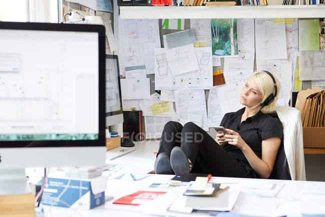 Женщина-дизайнер с ногами за столом — стоковое фото