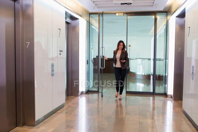 Businesswoman going through office door — Stock Photo