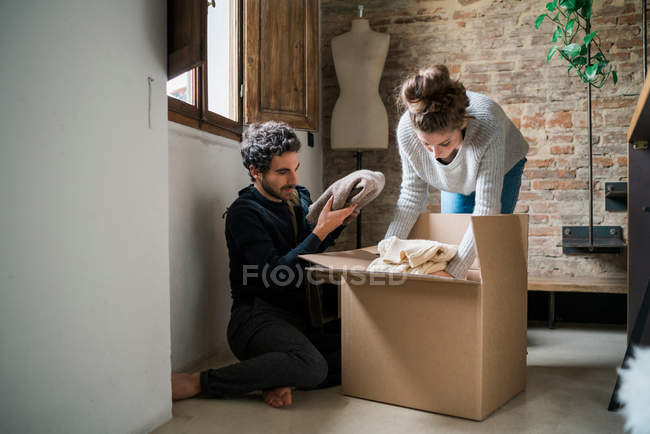 Couple packing cardboard box on floor — Stock Photo
