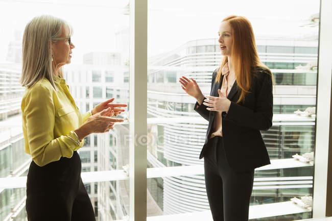 Деловые женщины разговаривают через окно — стоковое фото