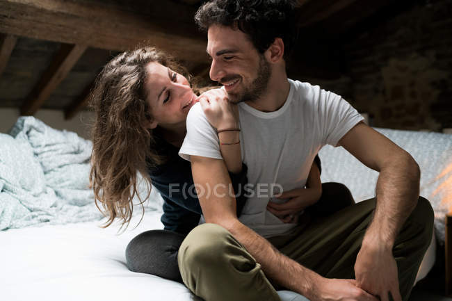 Couple sitting on bed and hugging — Stock Photo