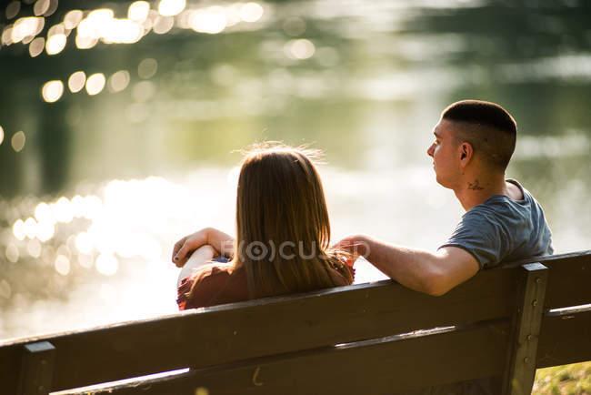 Paar sitzt auf Bank neben Fluss — Stockfoto