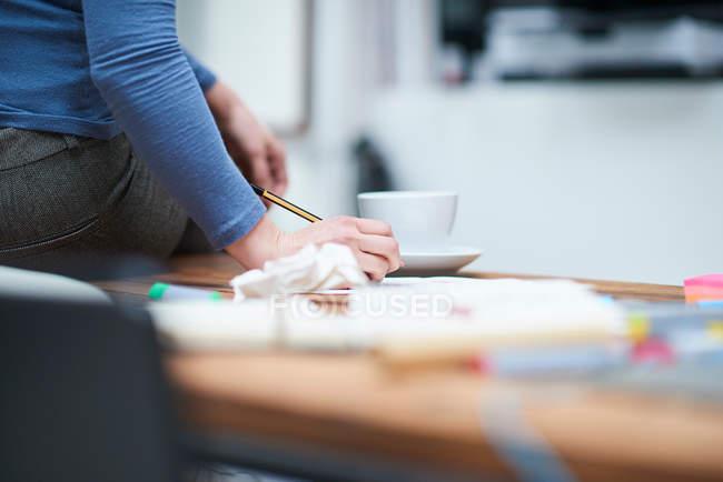 Female designer writing notes — Stock Photo