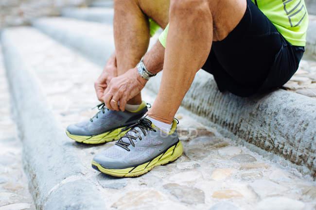 Homme attachant des lacets sur les chaussures de course — Photo de stock