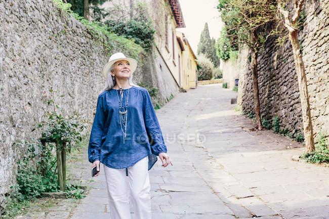 Зрелая женщина прогуливается по мощеной улице — стоковое фото