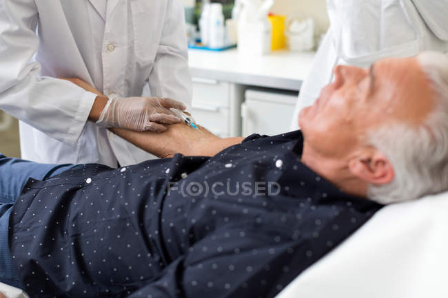 Doctor extracting patient's blood with syringe — Stock Photo
