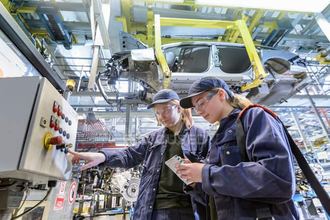 Ingenieros de mantenimiento femeninos en fábrica de automóviles - foto de stock