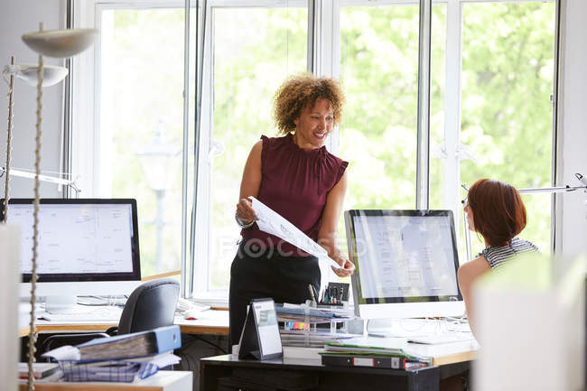 Female designers looking at blueprint — Stock Photo