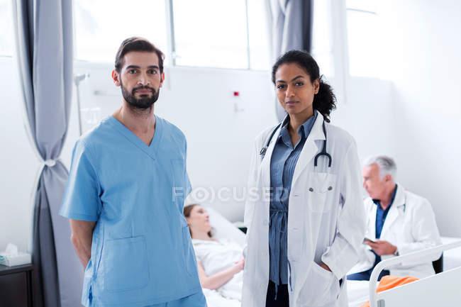 Лікарі в лікарні, дивлячись на камеру — стокове фото