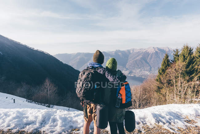 Hiking couple looking out over lake and mountains — Stock Photo