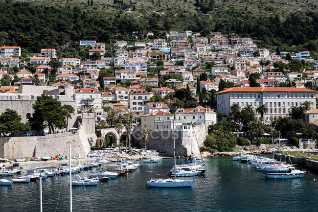 Прибрежный городской пейзаж с городскими стенами и причалом для яхт — стоковое фото