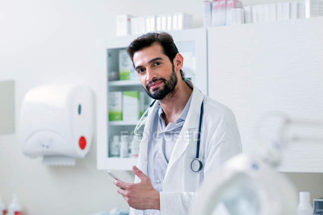 Doctor in hospital holding mobile phone — Stock Photo
