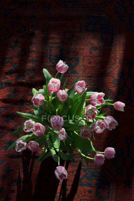 Tulip flowers arrangement on carpet — Stock Photo