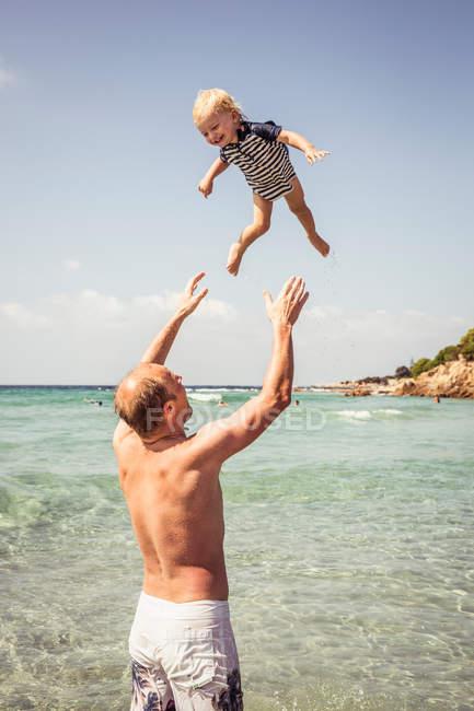 Pai jogando jovem filho no ar — Fotografia de Stock