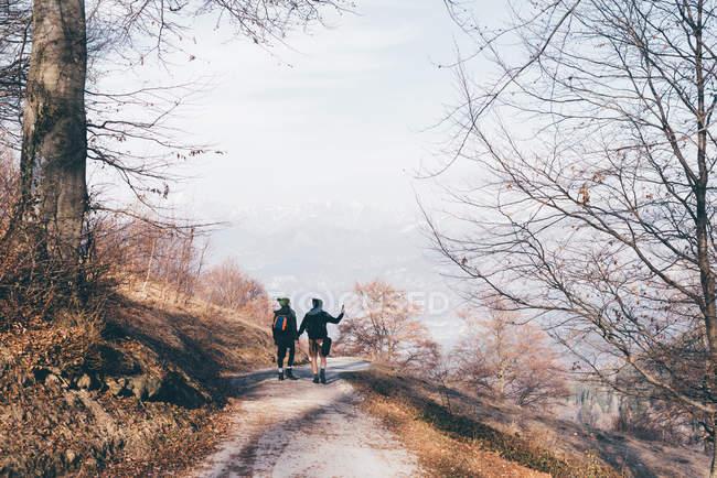 Wandern paar Wandern entlang Landstraße — Stockfoto