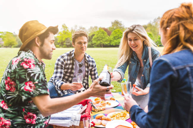 Group of friends pouring champagne — Stock Photo
