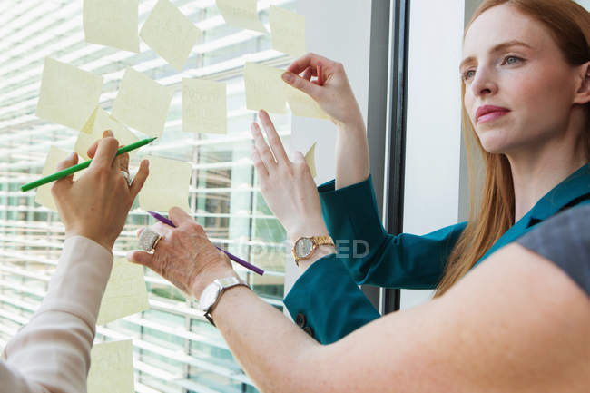 Businesswomen brainstorming ideas on glass window — Stock Photo