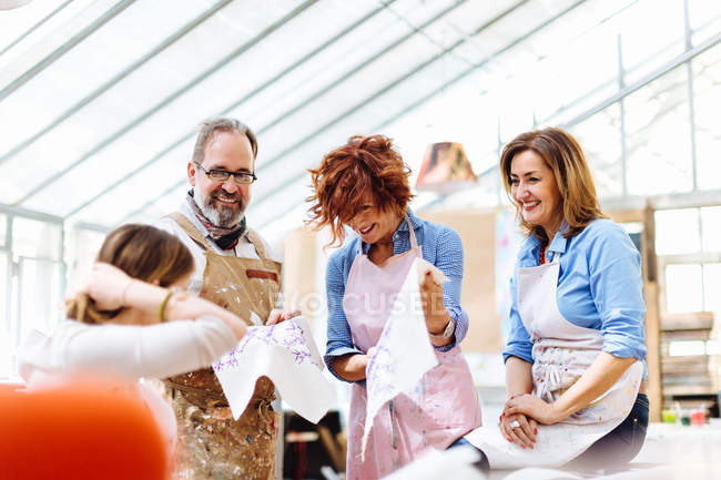 Group of artists looking at painted fabric — Stock Photo