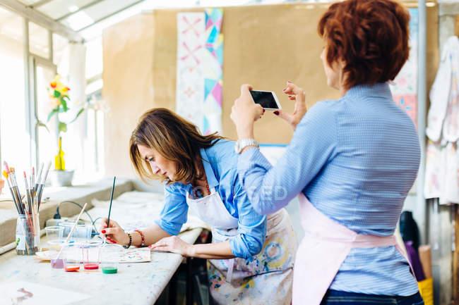 Artist painting on fabric in creative studio — Stock Photo