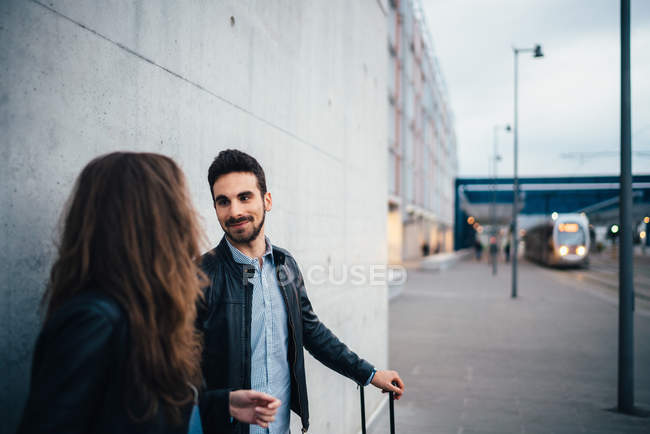 Couple standing by grey wall — Stock Photo