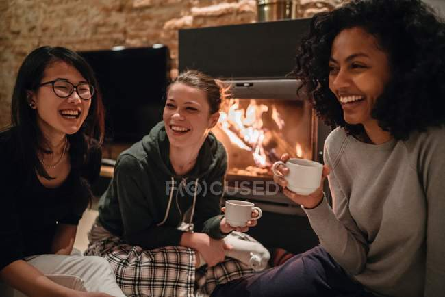 Friends in front of fire drinking coffee — Stock Photo