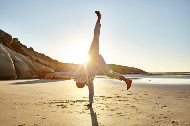 Зрелый человек делает колесо на пляже — стоковое фото