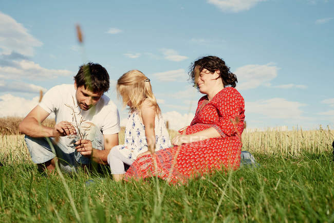 Couple sitting with toddler daughter — Stock Photo