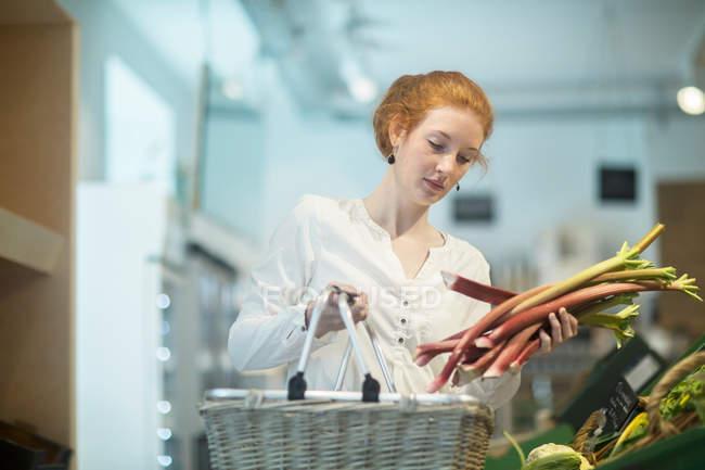 Donna nel negozio che tiene il carrello della spesa — Foto stock