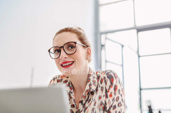 Woman in office wearing reading glasses — Stock Photo