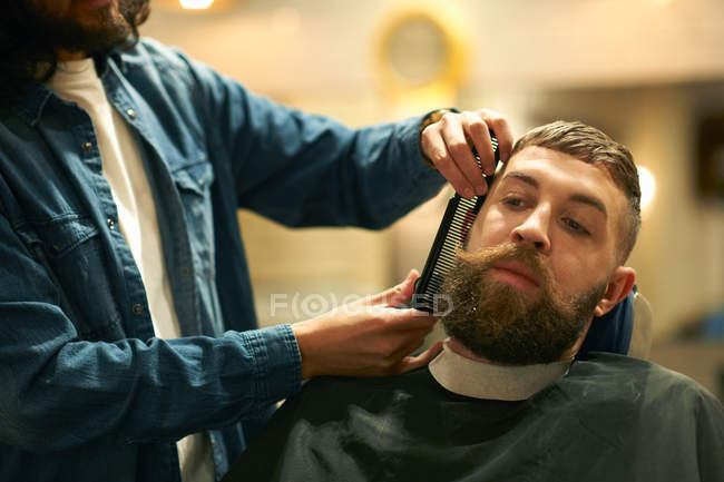 Hairdresser in barbershop trimming beard — Stock Photo