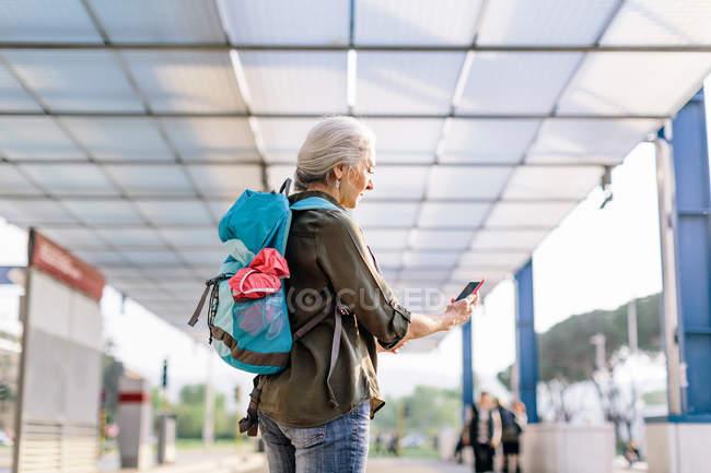Zaino in spalla femminile guardando smartphone — Foto stock