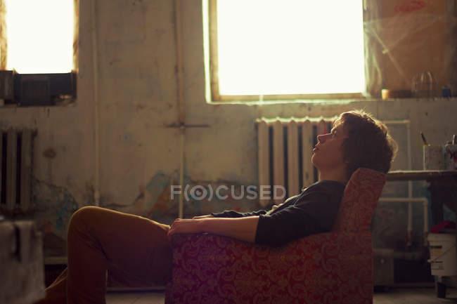 Jovem sentado na poltrona vintage — Fotografia de Stock