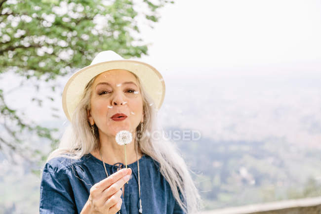 Mature woman blowing dandelion clock — Stock Photo