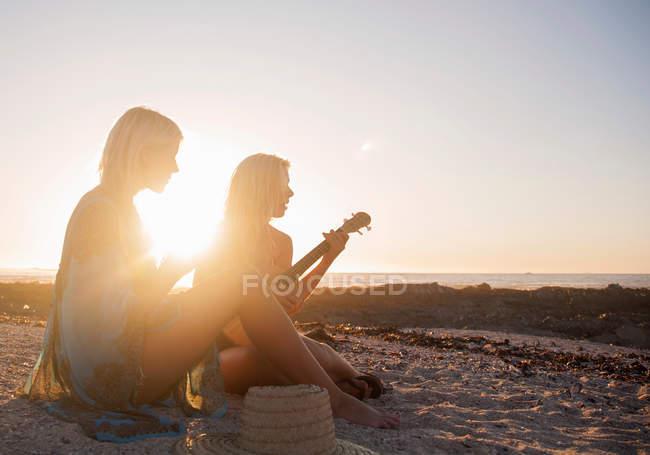 Women sitting on beach at sunset — Stock Photo