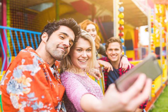 Gruppo di amici che si fanno selfie al luna park — Foto stock