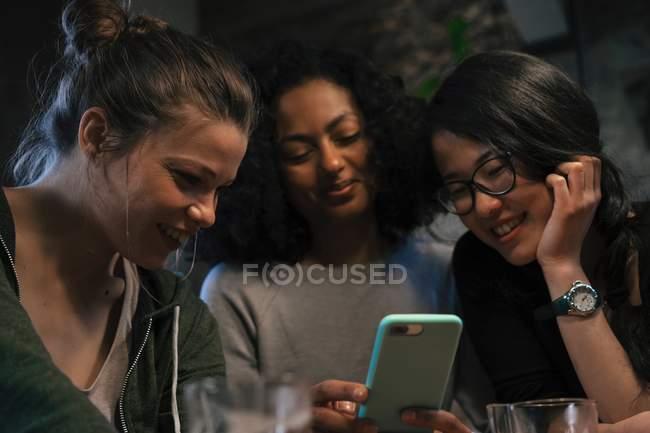 Freunde Blick auf Handy — Stockfoto