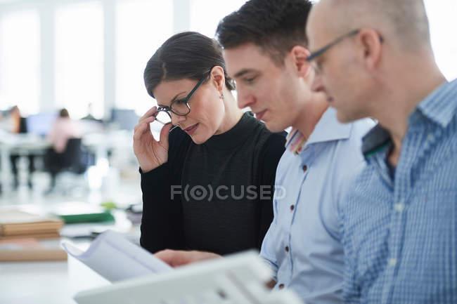 Colleghi in ufficio guardando modello architettonico — Foto stock