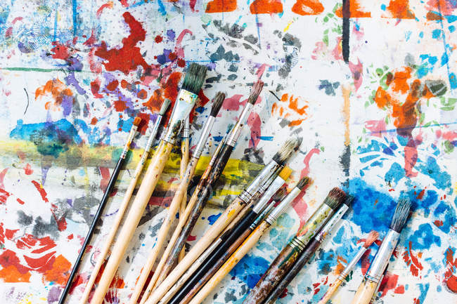Paintbrushes on colourful painted surface — Stock Photo