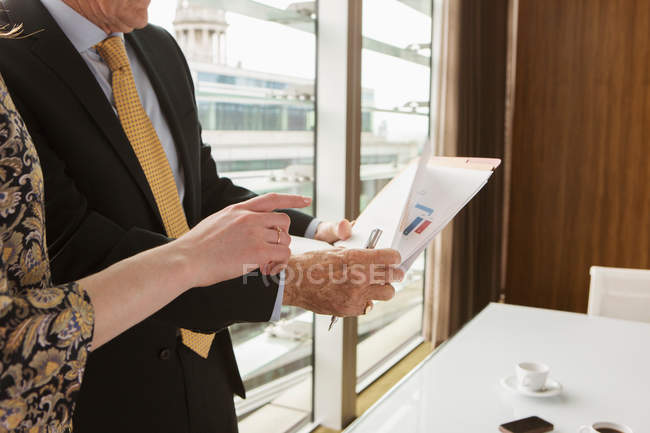Businessman and businesswoman reading — Stock Photo