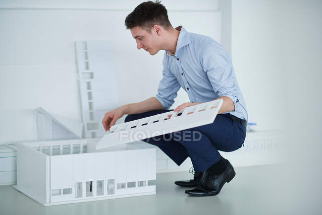 Architect in office looking at architectural model — Stock Photo