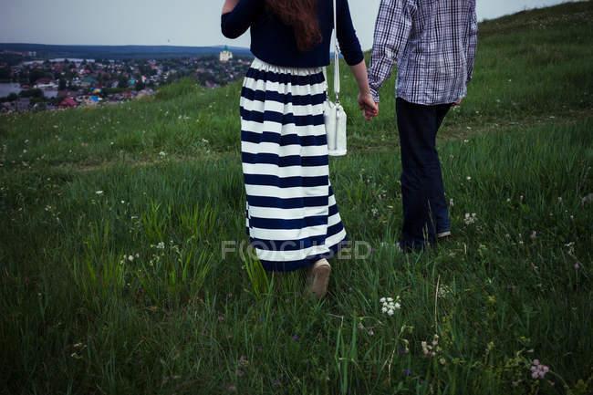 Giovane coppia a piedi lungo la collina erbosa — Foto stock
