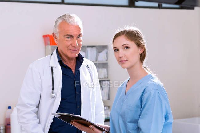 Doctors in clinic looking at camera — Stock Photo