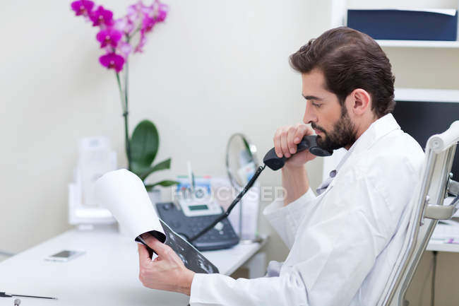 Doctor at desk making telephone call — Stock Photo
