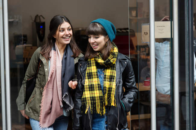 Women chatting while leaving cafe — Stock Photo