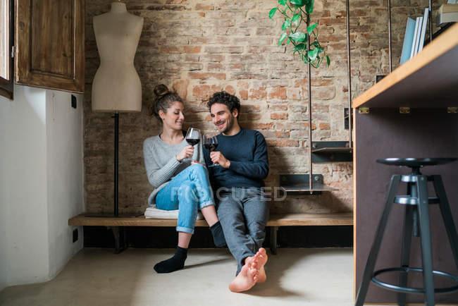 Couple raising toast on kitchen bench — Stock Photo