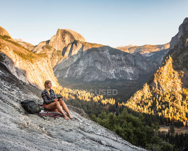 Woman looking out at valley forest — Stock Photo