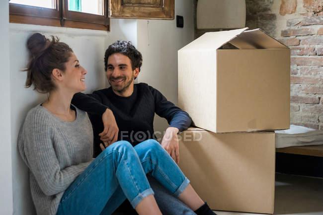 Coppia seduta sul pavimento da scatole di cartone — Foto stock