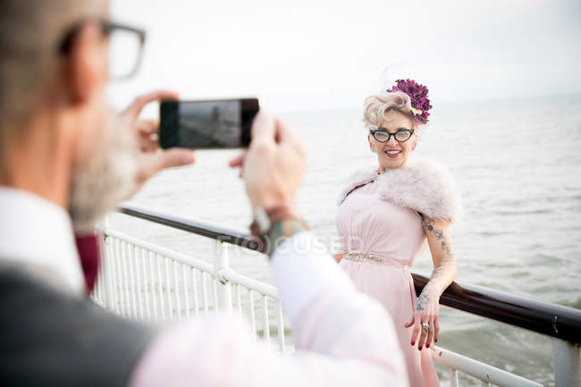 Man taking photograph of woman on pier — Stock Photo
