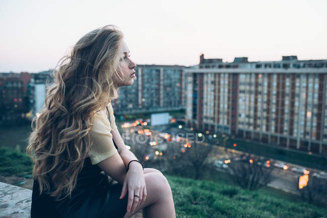 Young woman sitting on rooftop — Stock Photo